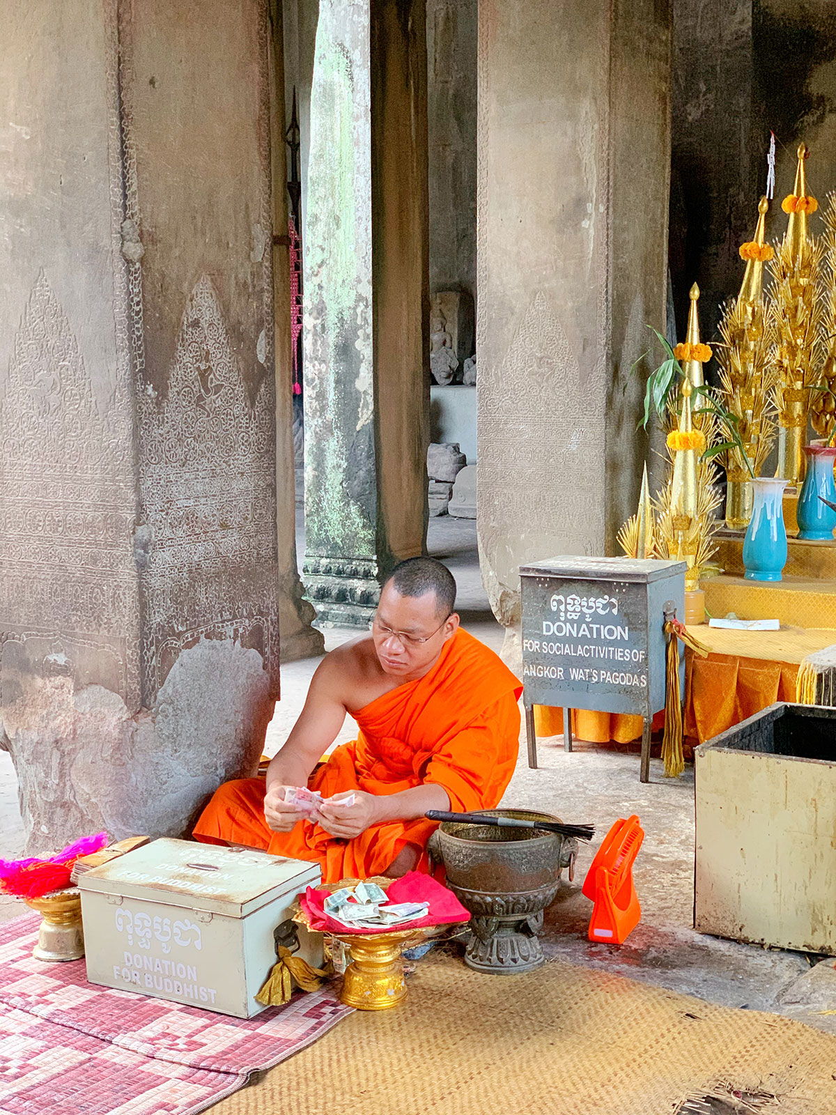 Buddhist monk counting money Angkor Wat