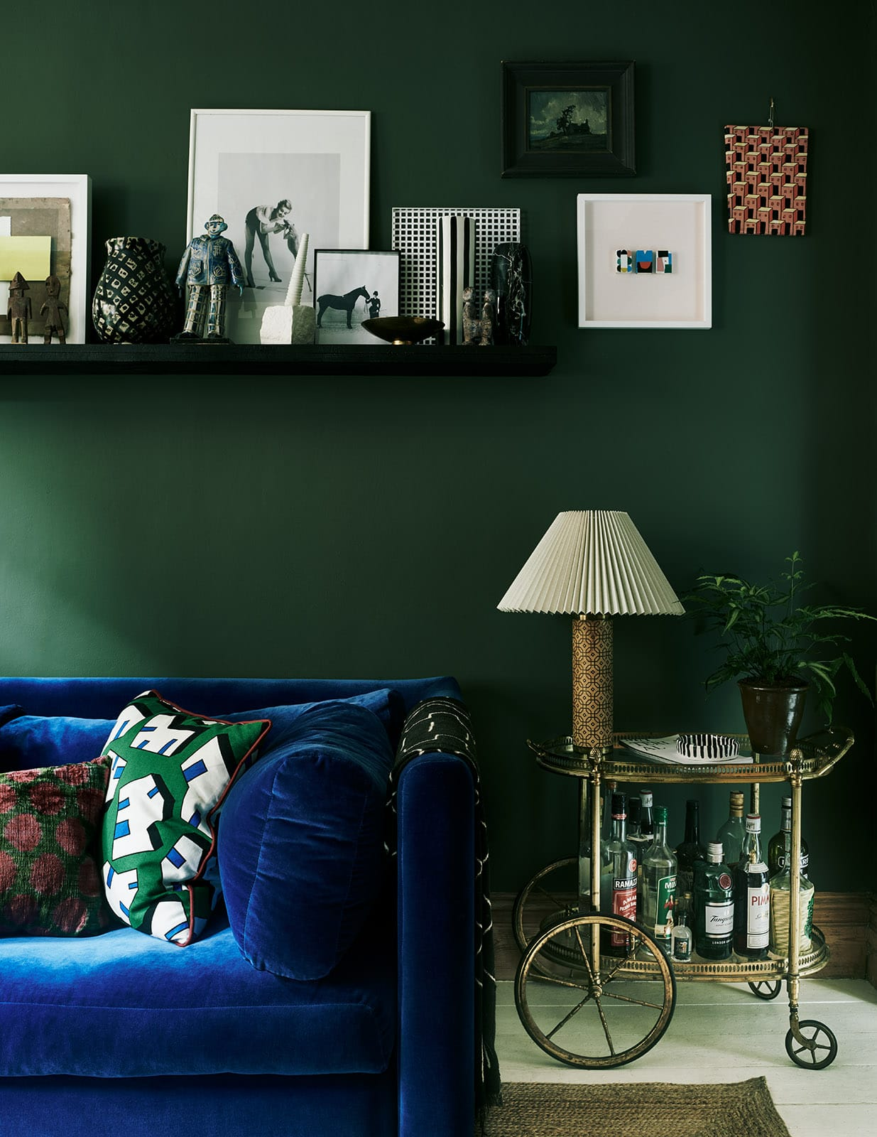 Jewel tone interior design Laura Fulmine, blue couch, emerald walls, bar cart.