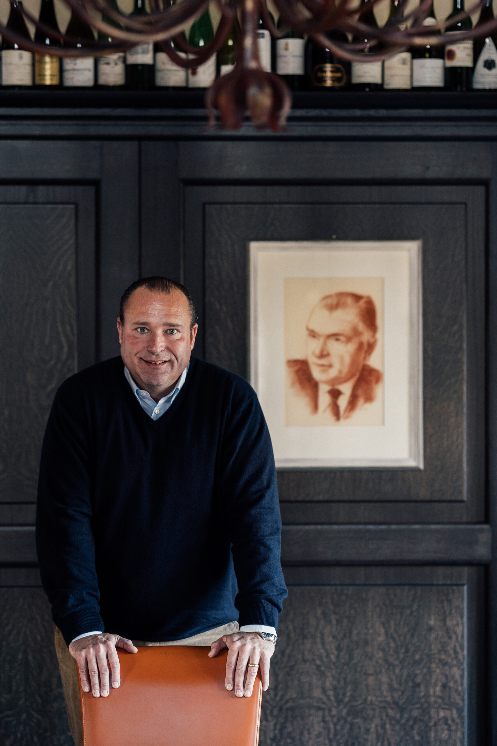 Nik Weis owner of a German winery, posing in front of a potrait of his grandfather.