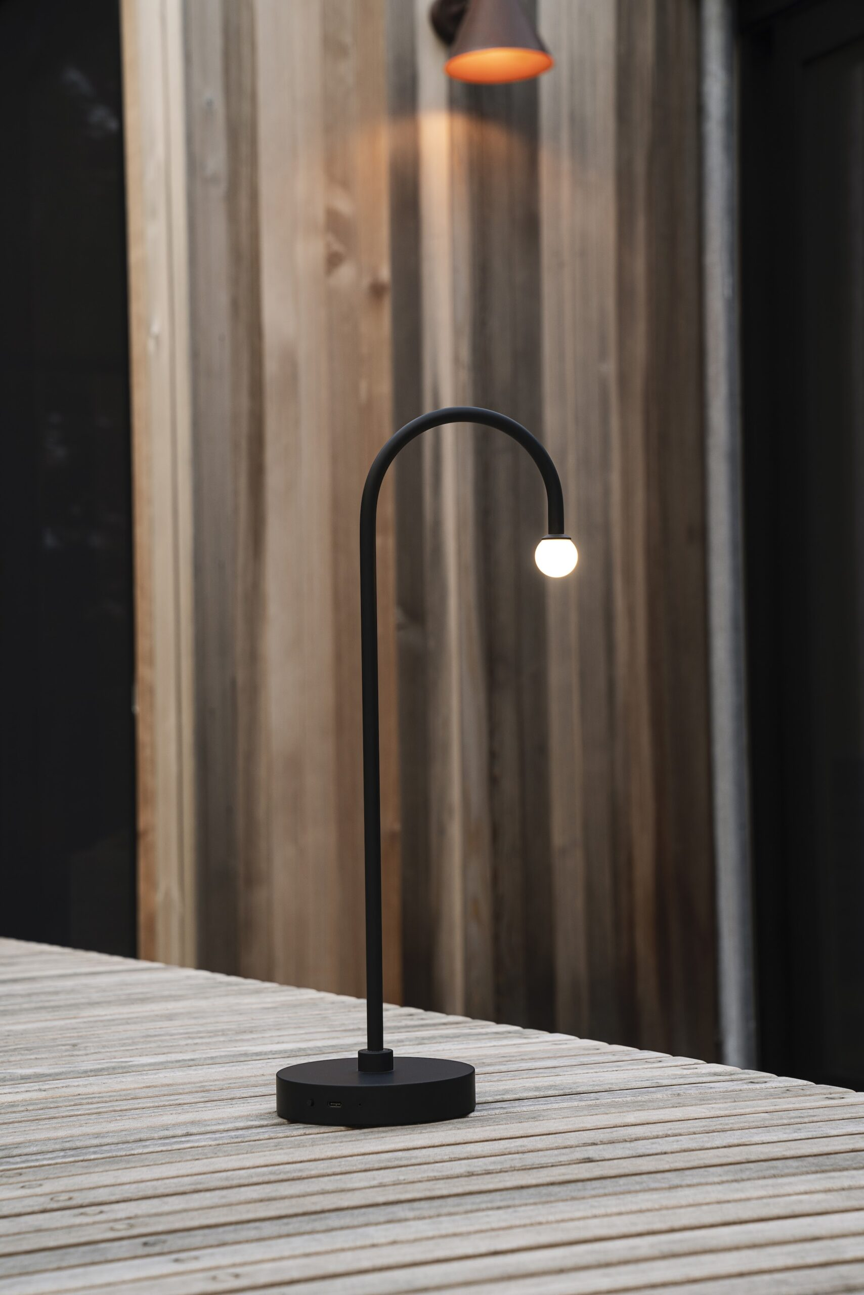 Thin black table lamp with small hanging bulb. Minimalist furniture.