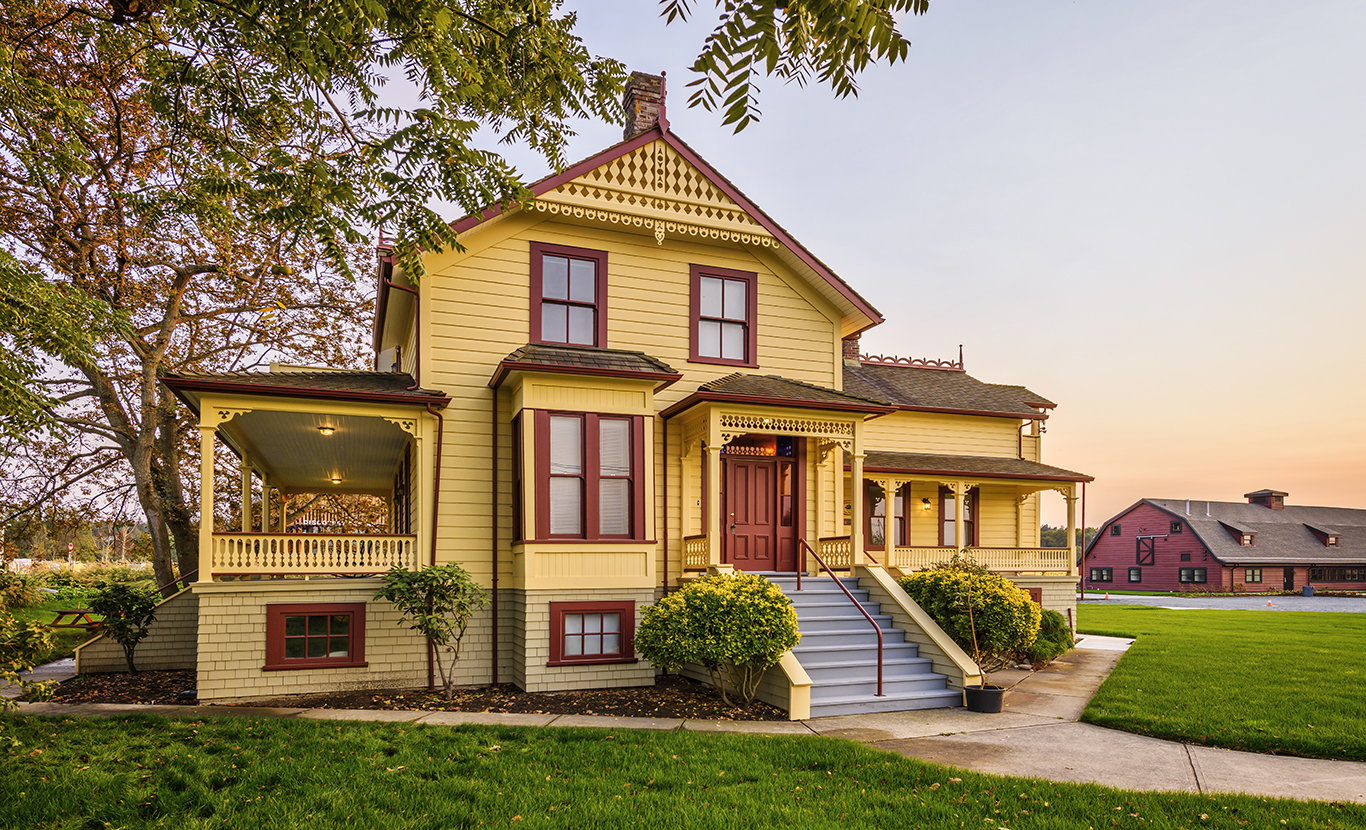 Agricommunity yellow colonial house with red trim